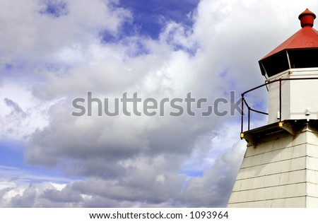 Clouds over a lighthouse by the ocean