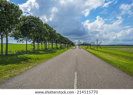 Clouds over a road through the countryside - stock photo