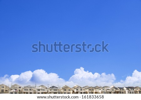 Clouds over houses in a row - stock photo