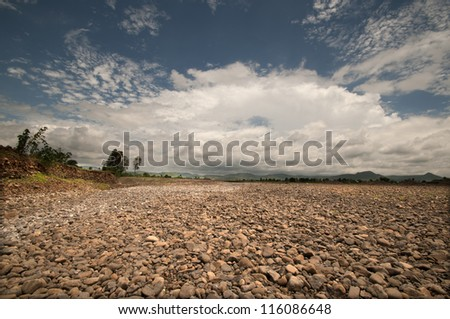 Clouds over rural stone ground - stock photo