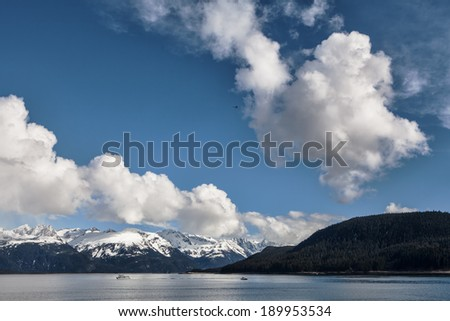 Clouds over the Lynn Canal from Picture Point near Haines Alaska with small fishing boats and an airplane. - stock photo