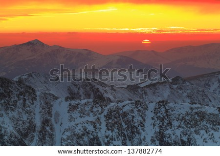 Clouds over the snowy mountains at sunset - stock photo