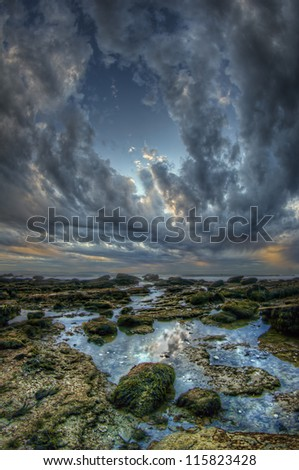 Clouds parting over rocky coast - stock photo