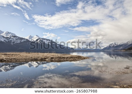 Clouds reflected in the Chilkat Inlet near Haines Alaska with mountains in the background. - stock photo