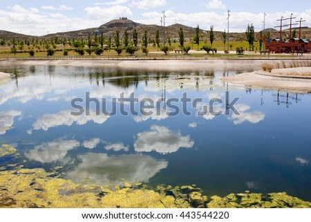 clouds reflecting in a lake of a park in summer