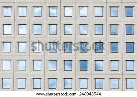 Clouds reflection on windows at office building - stock photo