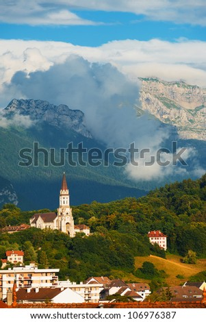 Clouds roll over the mountain behind the Basilica de la Visitation church surrounded by the green tree covered French Alps in Annecy, France. Vertical copy space compressed using telephoto lens