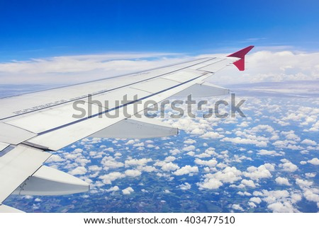 Clouds, sky and aircraft wing seen from airplane window.