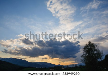 Clouds stretching across the sky at sunset - stock photo