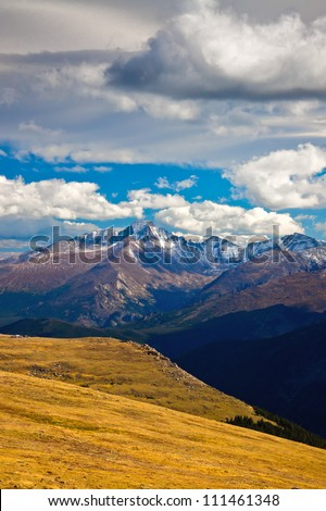 Clouds swoop by and over 14,259 feet high Longs Peak on a gorgeous autumn day in Rocky Mountain National Park, Colorado along Trail Ridge Road - stock photo