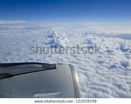 Cloudscape and engine seen through an airplane window - stock photo