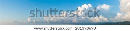 Cloudscape horizontal banner or panorama of beautiful fluffy white cumulus clouds in a sunny blue summer sky - stock photo