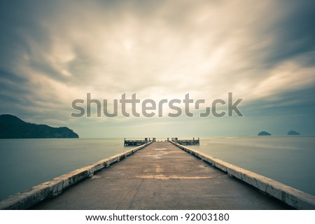 Cloudscape over sea with pier in foreground. - stock photo