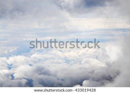 Cloudscape with an aerial view over the white cumulus cloud formations under a blue sky - stock photo