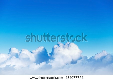 Cloudscape with white cumulus clouds in bright blue sky, natural photo background