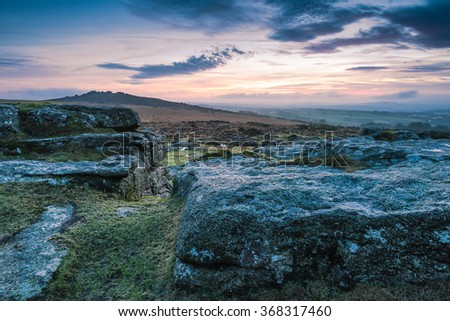 Cloudy and dramatic sky over granite rocks and hills in Dartmoor Park, UK - stock photo