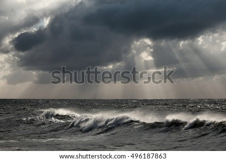 Cloudy autumn seascape with sunbeams, glistening sea, and a long wave in the foreground before rain and storm. Enhanced sky.
