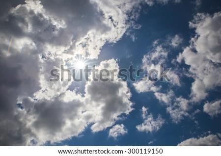 Cloudy blue sky and sun - stock photo