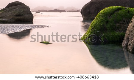 Cloudy Coastal Scene at Low Tide with rocks on the Coast of France - stock photo