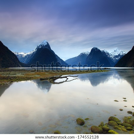 Cloudy day at Milford Sound, New Zealand. Calm lake produce reflection of Mitre Peak - stock photo
