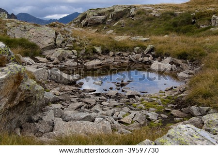 Cloudy day in Pyrenees - Andorra. Puddle on the meadow. - stock photo