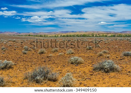 Cloudy desert landscape wtith mountain ranges in background