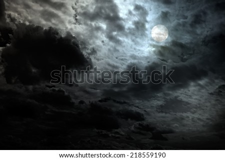 Cloudy full moon night with interesting light - stock photo