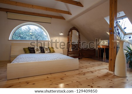Cloudy home - original wooden bedroom with arch window - stock photo
