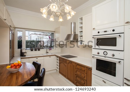Cloudy home - practical and well-furnished kitchen - stock photo