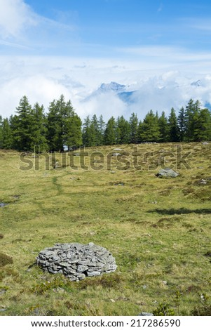 Cloudy L'Arpille Mountain seen from La Giete, in Switzerland, with pine trees and rocks in the foreground. - stock photo