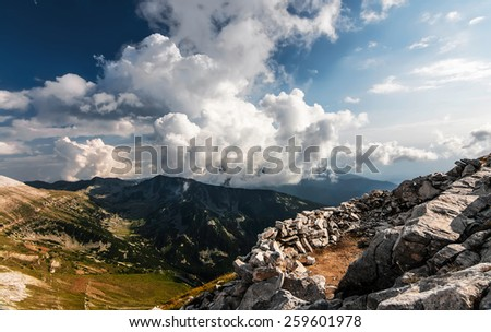 Cloudy mountain valley and a man made pile of rocks, cleared space for a tent - stock photo