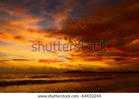 Cloudy orange sunset over sea - stock photo