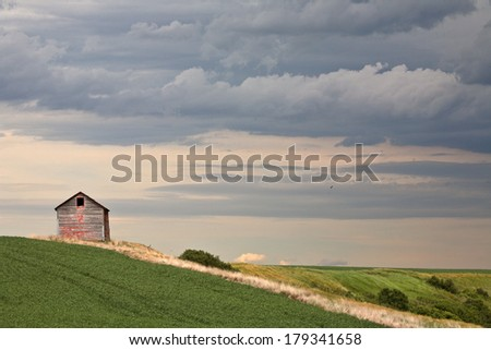 Cloudy skies over an old Saskatchewan granary - stock photo
