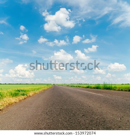 cloudy sky and asphalt road to horizon - stock photo