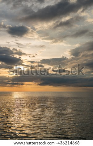 cloudy sky at sunset reflected in a sea of steel-colored - stock photo