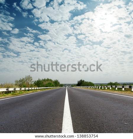 cloudy sky over asphalt road - stock photo