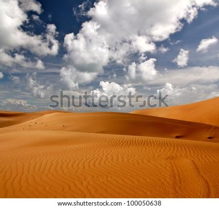 Cloudy sky over sand dune desert - stock photo