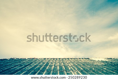 Cloudy sky over the asbestos roof tiles processed in vintage style able to use as background - stock photo