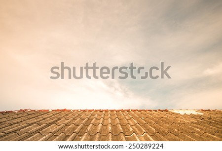Cloudy sky over the asbestos roof tiles processed in warm tone able to use as background - stock photo