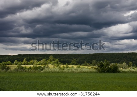 Cloudy sky over the meadows in the day afternoon - stock photo