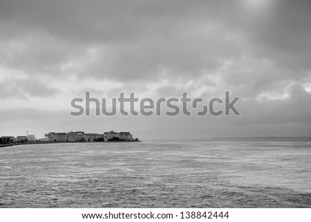 Cloudy sky over water with vacation homes. - stock photo