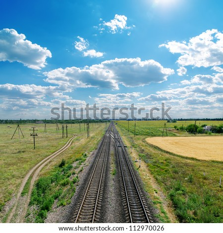 cloudy sky with sun over railroad