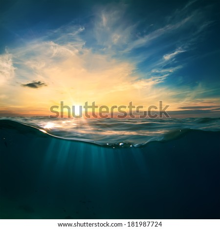 Cloudy sky with the sun split by waterline to underwater scene as design template. - stock photo