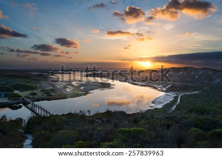 Cloudy sunrise over a quiet lagoon with cloud patterns reflected in the water