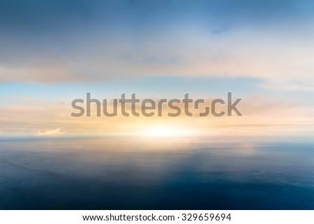 Cloudy sunrise sky and calm sea landscape - stock photo