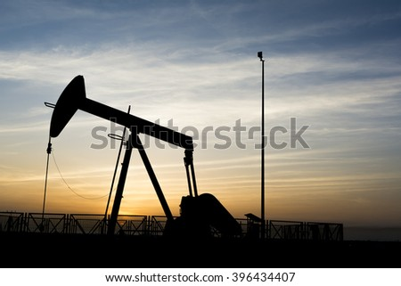 Cloudy sunset and silhouette of crude oil pump in oil field