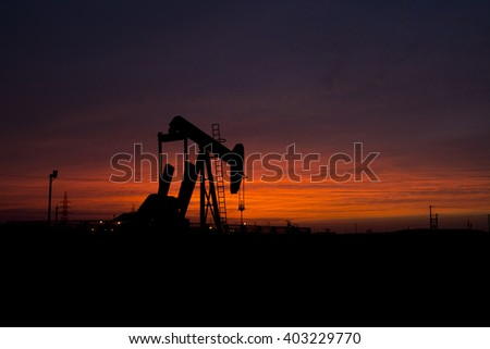 Cloudy sunset and silhouette of crude oil pump in oilfield.    - stock photo