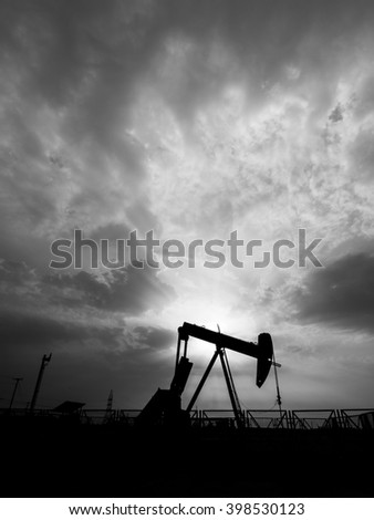 Cloudy sunset and silhouette of crude oil pump in oilfield - Black and white