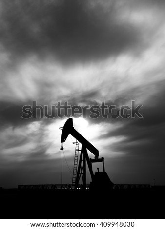 Cloudy sunset and silhouette of crude oil pump in oilfield - black and white  - stock photo
