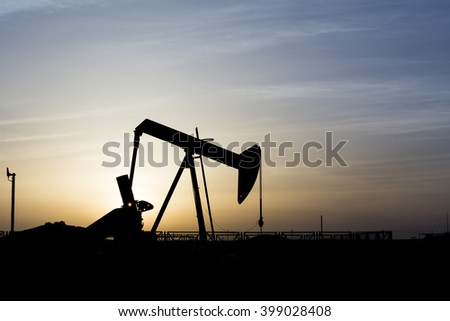 Cloudy sunset and silhouette of crude oil pump in the oil field.